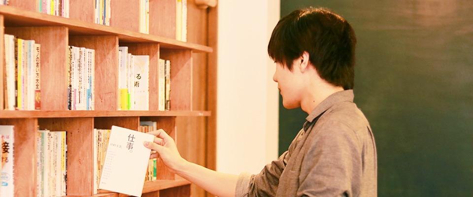 本を手に取る男性