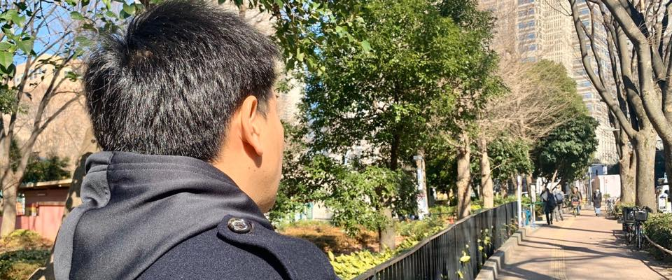 公園の横で向こうを見つめる男性