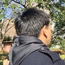 フード付きパーカーを着た男性の後ろ姿