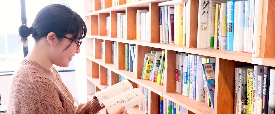本棚の前で本を読む女性