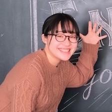 笑顔で笑うメガネをかけた黒髪の女性